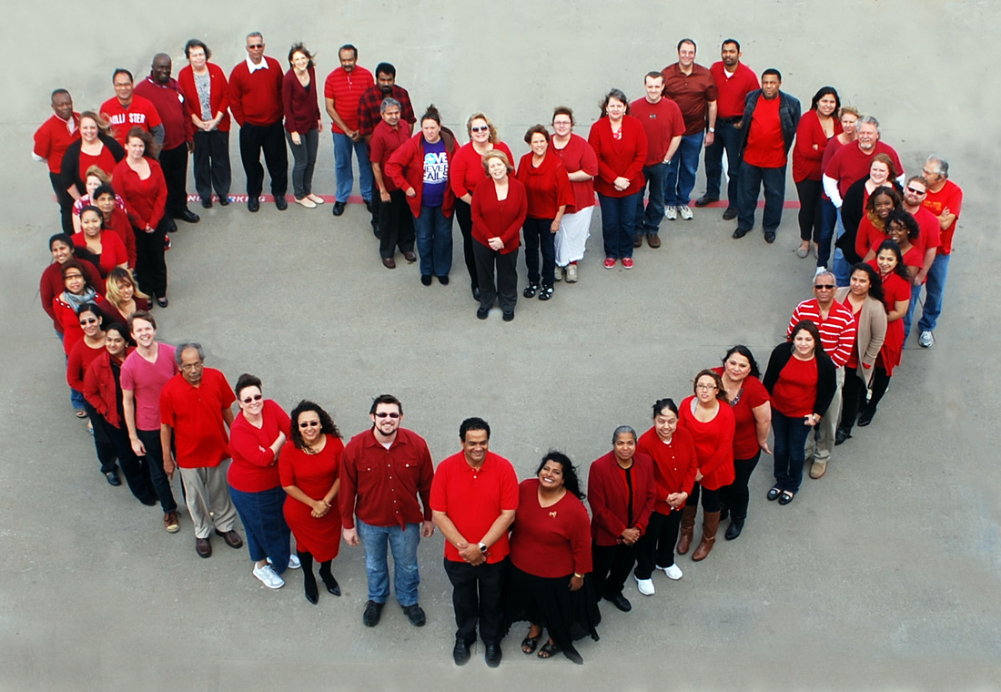 Agape Home Health office staff stand in a heart shaped formation for the American Heart Association's National Wear Red Day